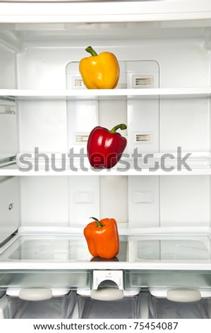 Refrigerator close up with three pepper - stock photo