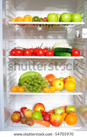 Refrigerator full of fruit and vegetables - stock photo