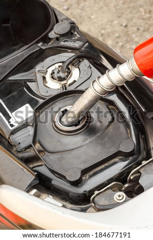 Refueling a motorcycle at a gas station  - stock photo
