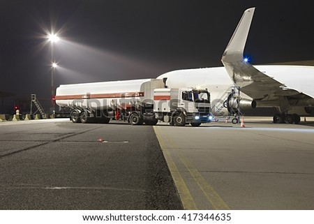 Refueling a plane at night - stock photo