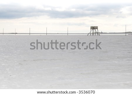 Refuge box on Pilgrims's Causeway, Lindisfarne, with tide in - stock photo