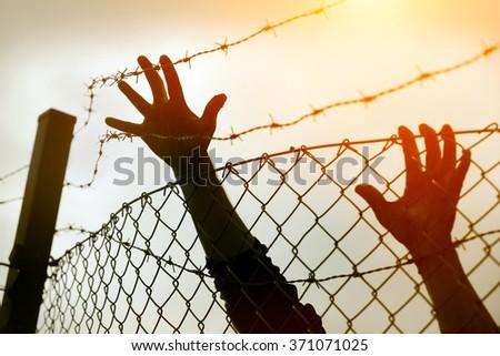 Refugee men and fence. Refugee concept - stock photo
