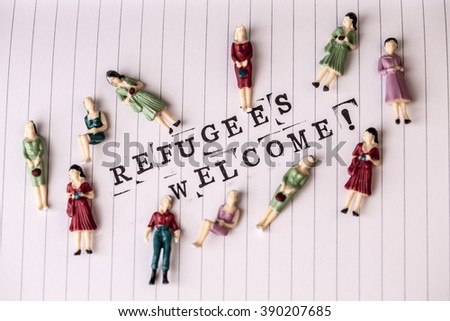 refugees welcome text on white line paper with woman figures around - stock photo