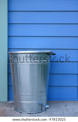 Refuse bin and blue wall - stock photo