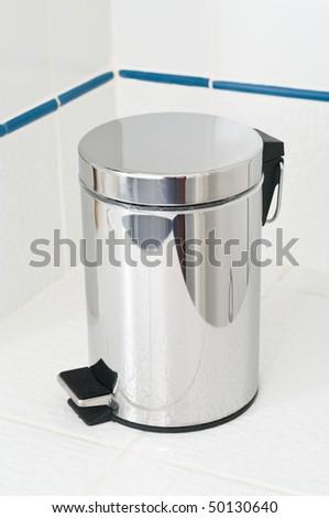 Refuse bin in room corner on white tile floor - stock photo