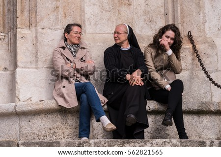 Regensberg, Germany - May 15, 2016 - Catholic nun and friends sitting outside of a cathedral in Regensberg, Germany