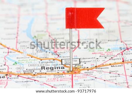 Regina in Saskatchewan, Canada. Red flag pin on an old map showing travel destination. - stock photo
