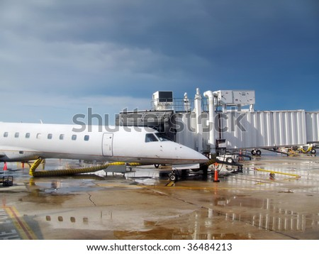 Regional jet parked on wet tarmac with dark clouds in the background. - stock photo