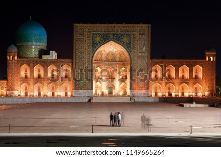 Registan Madrasah illuminated at night at Samarkand, Uzbekistan, Middle Asia. Selective focus, blurred with long shutter people's silhouettes