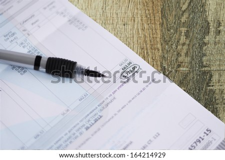 Regular invoice with the pen on wooden table - stock photo