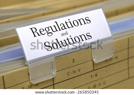 regulations and solutions printed on file folder with documents - stock photo