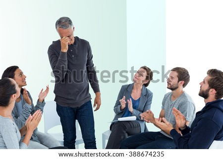 Rehab group applauding delighted man standing up against bright blue - stock photo