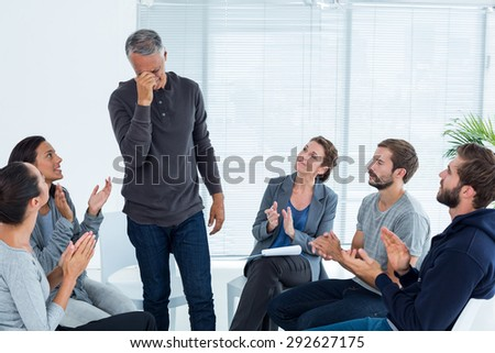 Rehab group applauding delighted man standing up at therapy session - stock photo