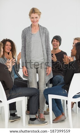 Rehab group applauding delighted woman standing up at therapy session - stock photo