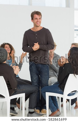 Rehab group applauding happy man standing up at therapy session - stock photo