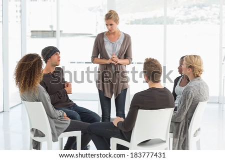 Rehab group listening to woman standing up introducing herself at therapy session - stock photo