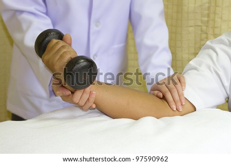 Rehab muscle training for elbow joint, physical therapist - stock photo