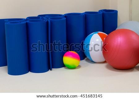 rehabilitation gym equiment: balls, mats, steps, mirror - stock photo
