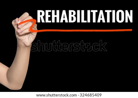 Rehabilitation word write on black background by woman hand holding highlighter pen - stock photo