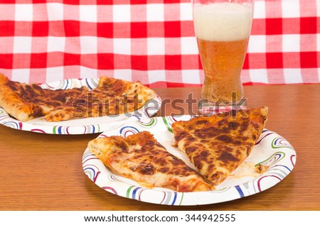 Reheated pizza served on paper plates with cold beer. - stock photo