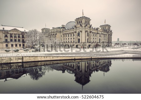 Reichstag building (Bundestag) and with reflection in river Spree in Winter, Berlin government district, Germany, Europe, Vintage filtered style
