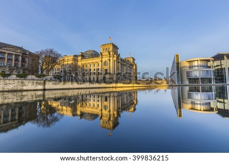 Reichstag with reflection in river Spree in early morning - stock photo