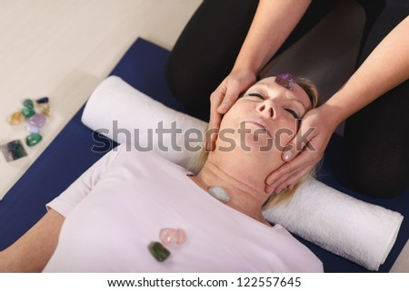 Reiki therapy with girl working as spirit healer, arranging crystals and gemstones on female client for treatment - stock photo