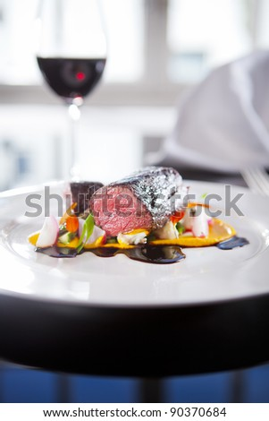 Reindeer fillet on white plate with yellow sauce - stock photo