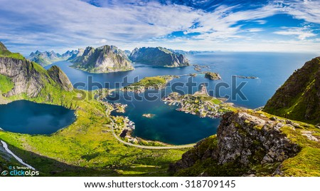 Reine, Lofoten, Norway. The village of Reine under a sunny, blue sky, with the typical rorbu houses. View from the top of Reinebringen mountain. - stock photo