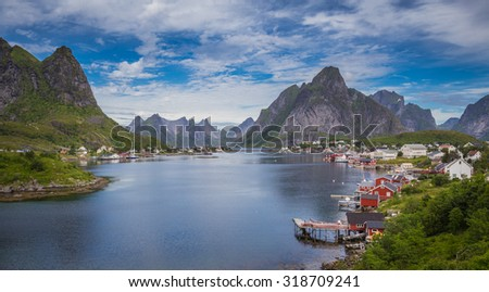 Reine, Lofoten, Norway. The village of Reine under a sunny, blue sky, with the typical rorbu houses. - stock photo
