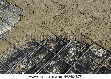Reinforcement steel mesh partly covered with fresh rough concrete slab. Construction background