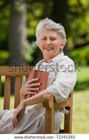 Reired woman reading a book on the  bench - stock photo