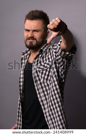 Rejection. Stylish young man showing his thumb down and smiling while standing against background - stock photo