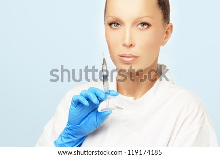 Rejuvenation.Attractive doctor prepare to Injection of beauty products.Blue background - stock photo