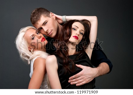 Relations between men and women love passion betrayal. Man and two women, blonde and brunette, love, sexy - the modern concept of love story for three people. Hatred between the two lovers.  - stock photo