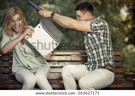Relationship and arque concept. Yong playful couple with book and computer sitting in the park and arquing. - stock photo