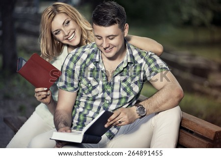 Relationship and education concept. Young happy couple of students are sitting on the bench in the park, learning, reading and smiling. - stock photo