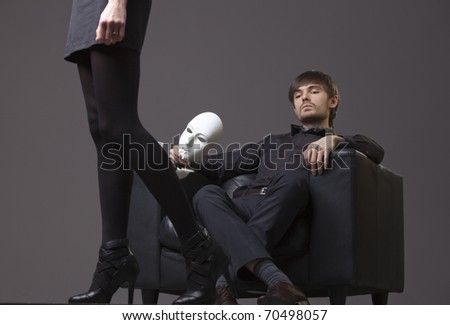 relationship conflict - man with mask treats woman with contempt - stock photo