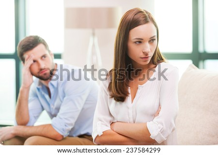 Relationship difficulties. Depressed young woman keeping arms crossed and looking away while man sitting behind her on the couch  - stock photo