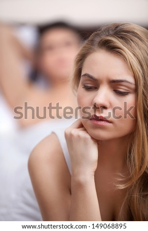 Relationship difficulties. Disappointed young woman sitting with her hand on chin and looking away while her boyfriend lying on the background - stock photo