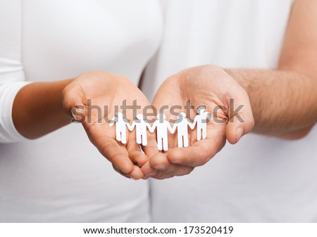 relationships and love concept - closeup of couple hands showing paper cutout team - stock photo