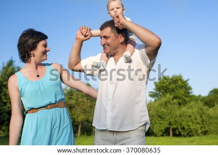 Relationships Concepts. Young Caucasian Family of Three People Having Good Time Together Outdoors. Horizontal Image - stock photo