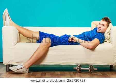 Relax after sport activity. Young man fit body relaxing on couch, dumb bell on floor - stock photo
