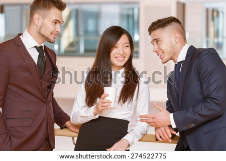 Relax at a coffee break.  Two handsome businessmen having an informal talk with a female colleague during the coffee break - stock photo