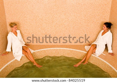 Relax bath spa two beautiful women sitting by water jacuzzi - stock photo
