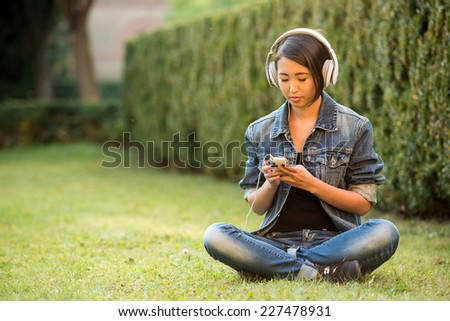 Relax. Beautiful smiling asian female student is sitting on the grass near the college and listening music.