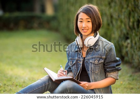 Relax. Beautiful smiling asian female student is sitting on the grass near the college and reading.