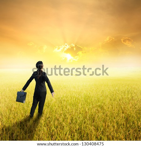 Relax business woman holding bag in yellow rice field and sunset - stock photo