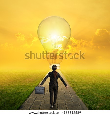 Relax business woman holding bag on Concrete road to Big idea bulb in Grass fields and sunset