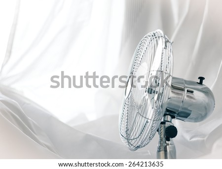 relax concept - metal fan near the window (small grip) - stock photo
